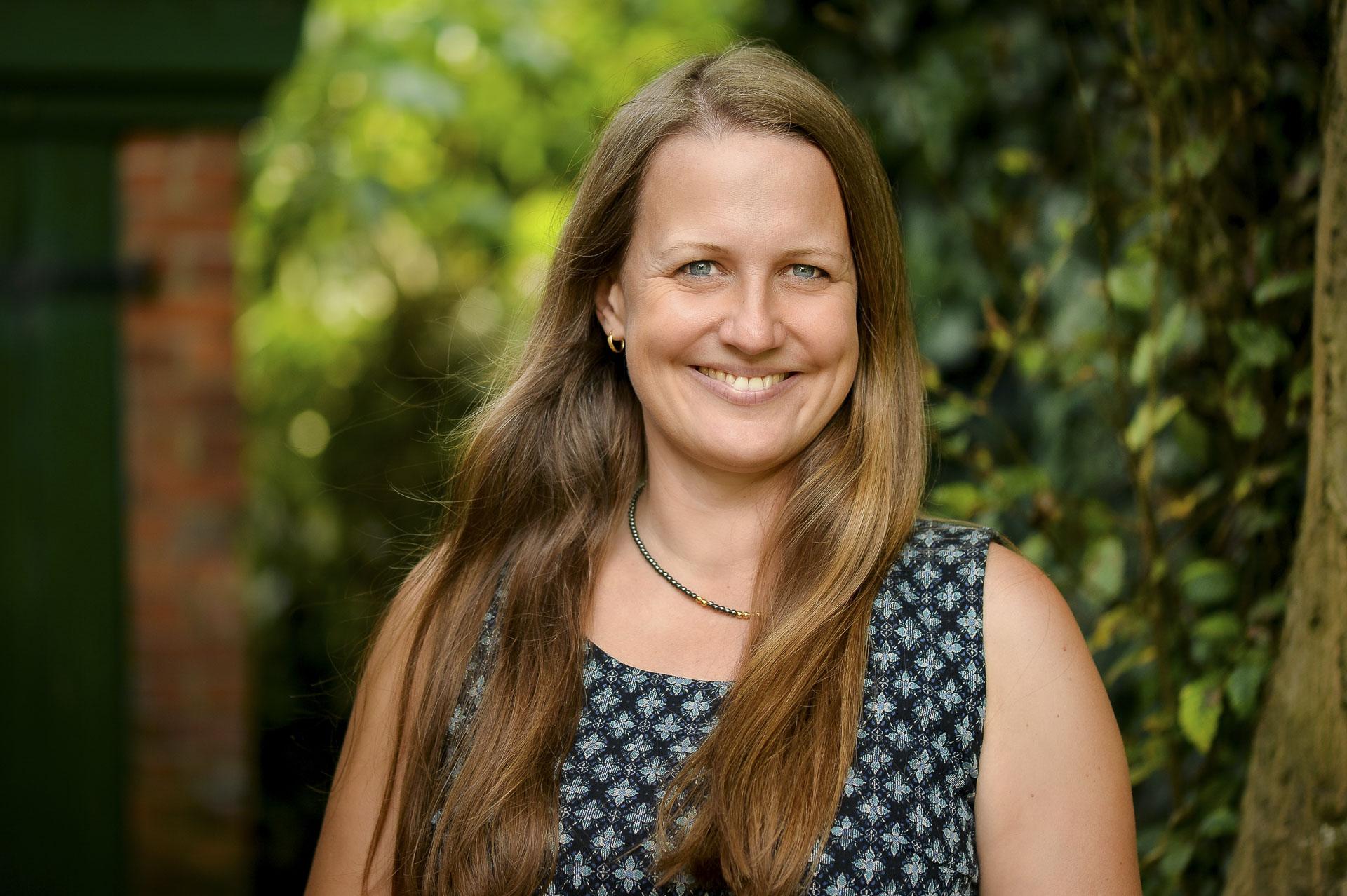 Eine Frau mit langen Haaren und Sommerkleid lächelt