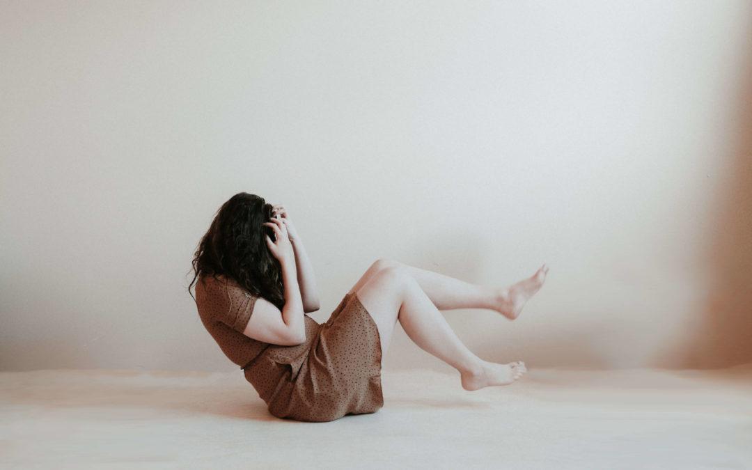Frau strampelt mit den Beinen und hält die Hände vors Gesicht. Die Farben des Bildes sind in sepia